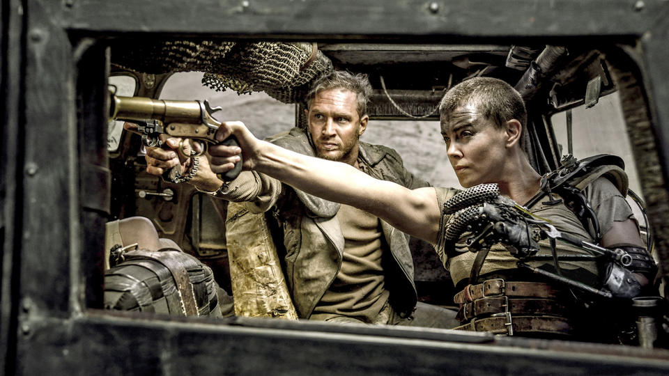 """(L-r) TOM HARDY as Max Rockatansky and CHARLIZE THERON as Imperator Furiosa in Warner Bros. Pictures' and Village Roadshow Pictures' action adventure """"MAD MAX: FURY ROAD,"""" a Warner Bros. Pictures release. from Warner Bros. media site"""